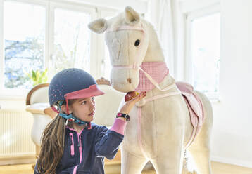 Girl feeding her toy horse at home - DIKF00462