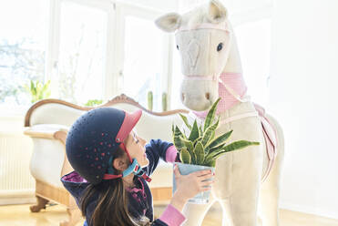 Girl feeding her toy horse with house plant at home - DIKF00465