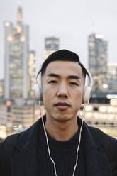 Portrait of man with headphones in front of urban skyline, Frankfurt, Germany - AHSF02256