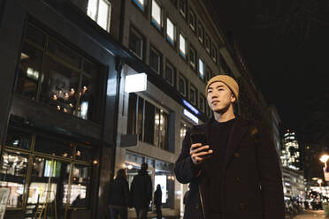Man using smartphone in the city at night - AHSF02268