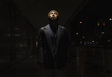 Portrait of stylish man with yellow hat and earphones with eyes closed in the city at night - AHSF02274