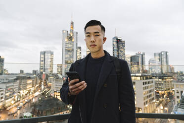Portrait of man holding smartphone in the city at dusk - AHSF02283