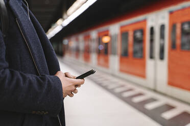 Close-up of man using smartphone in metro station - AHSF02292