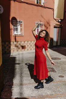 Young woman wearing red dress and dancing - TCEF00510