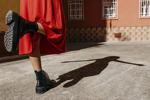 Young woman wearing red dress and black boots, playing with her shadow on the floor - TCEF00516