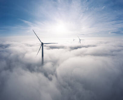 Germany, Aerial view of wind turbines shrouded in clouds at sunrise - WFF00330