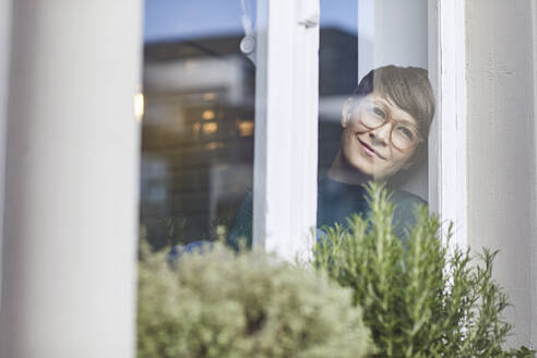 Smiling woman at home looking out of window - MCF00658