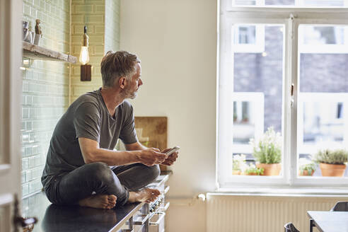 Mature man with cell phone sitting on kitchen counter at home - MCF00682
