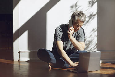 Mature man sitting on the floor at home using laptop and cell phone - MCF00694