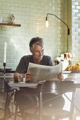 Mature man sitting in kitchen reading newspaper - MCF00703