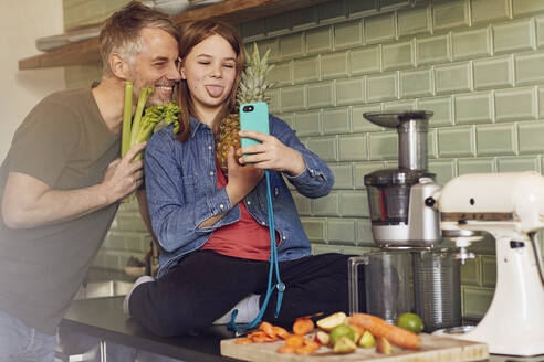 Happy father and daughter in kitchen making a selfie with fruit and vegetable - MCF00718