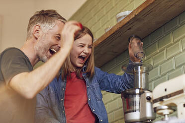 Playful father and daughter in kitchen preparing a smoothie - MCF00721
