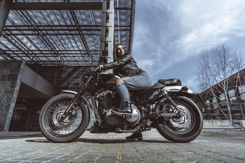 Confident young woman on motorcycle - DAMF00374