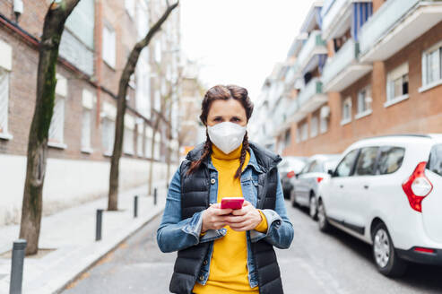 Woman wearing protective mask and using smartphone - JCMF00586