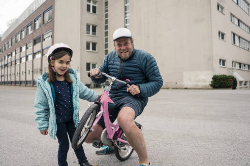Playful father with daughter on her bicycle - JOSEF00289