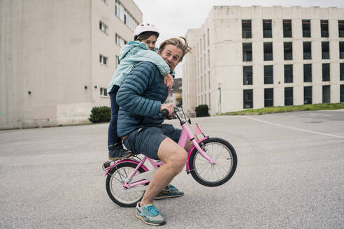 Playful father with daughter on her bicycle - JOSEF00292