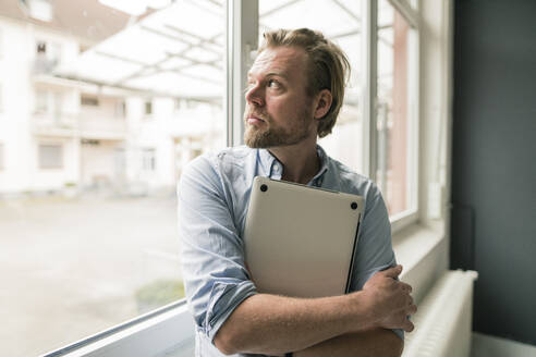 Casual businessman with laptop looking out of window - JOSEF00298