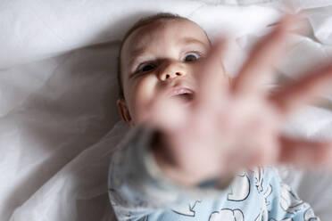 Baby girl teething, lying on bed - GEMF03602