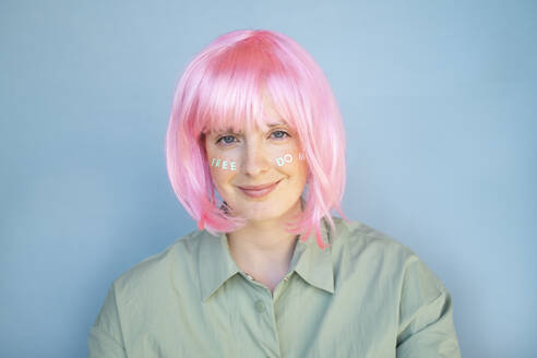 Young woman wearing pink wig, letters on her face, freedom - AFVF06104