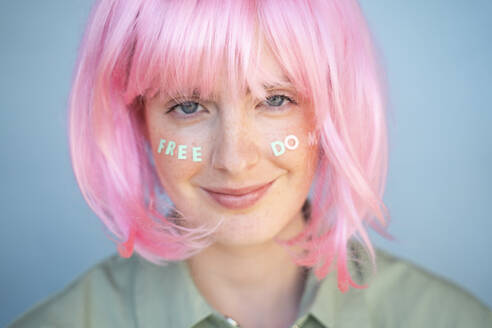 Young woman wearing pink wig, letters on her face, freedom - AFVF06107