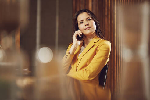Businesswoman on the phone wearing yellow suit sitting at desk in office - MCF00744