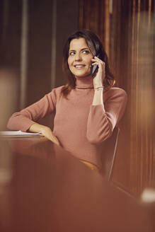 Smiling businesswoman on the phone sitting at desk in office - MCF00759