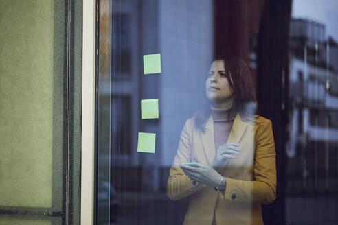 Portrait of businesswoman wearing yellow suit standing behind windowpane - MCF00762