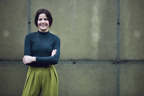 Portrait of smiling businesswoman standing at a green wall - MCF00771