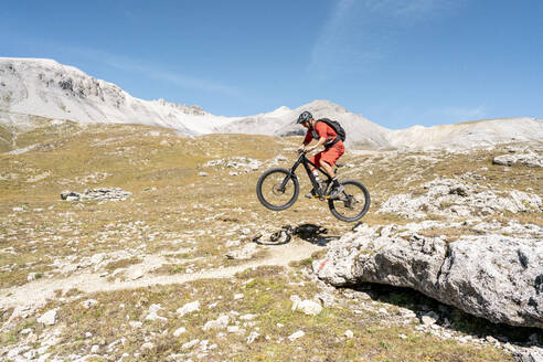 Man riding on mountainbike, Munestertal Valley, Grisons, Switzerland - HBIF00104