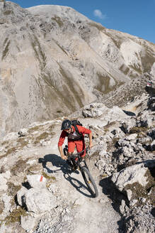 Man riding on mountainbike, Munestertal Valley, Grisons, Switzerland - HBIF00107