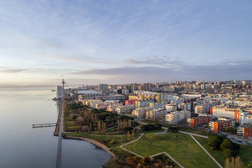 Portugal, Lisbon, Drone view of residential district of coastal city at dusk - RPSF00286