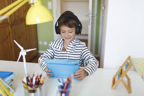 Boy doing homeschooling and using tablet and headphones at home - HMEF00896