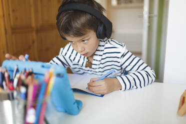 Boy doing homeschooling and writing on notebook, using tablet and headphones at home - HMEF00899
