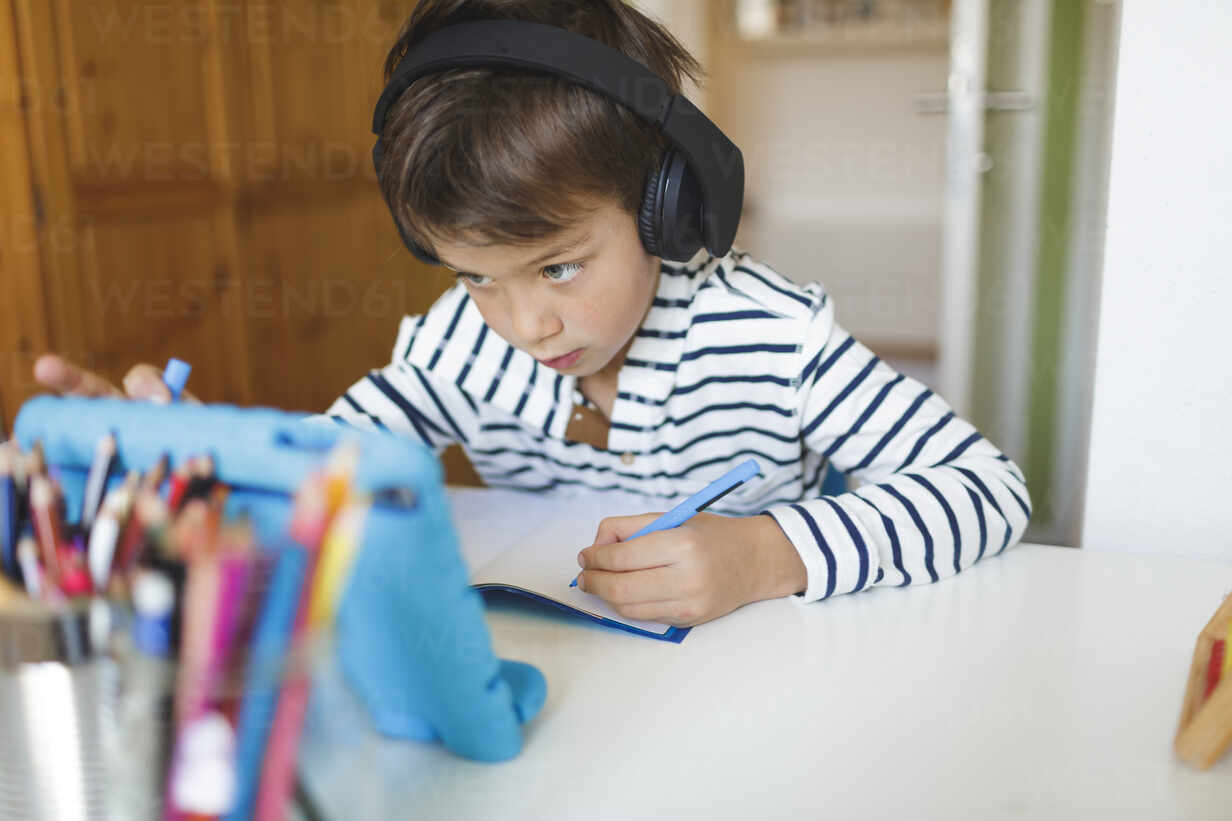 Boy doing homeschooling and writing on notebook, using tablet and headphones at home - HMEF00899 - Epiximages/Westend61