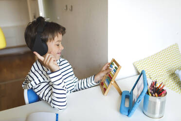 Boy doing homeschooling and using slide rule, tablet and headphones at home - HMEF00902