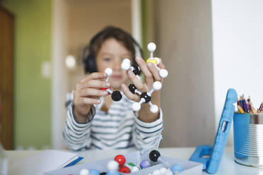 Boy doing homeschooling and holding molecule model, using tablet and headphones at home - HMEF00905