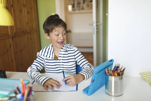 Boy doing homeschooling and writing on notebook, using tablet and headphones at home - HMEF00908