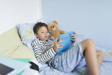 Boy lying in bed using digital tablet - HMEF00914