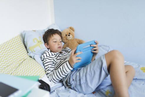 Boy lying in bed using digital tablet - HMEF00914