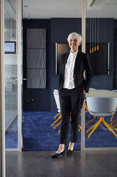 Portrait of fashionable senior businesswoman wearing black pantsuit in office - RBF07603