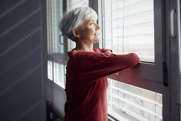 Portrait of senior woman looking out of window - RBF07606