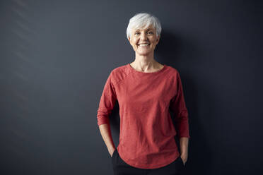 Portrait of smiling senior woman wearing red shirt standing in front of grey wall - RBF07609