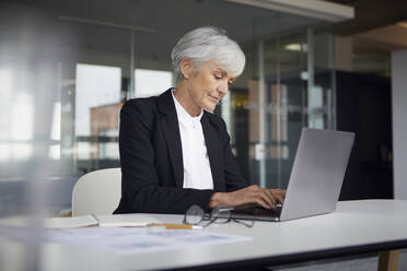 Senior businesswoman sitting at desk working on laptop - RBF07612