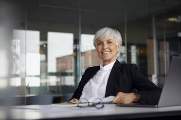 Portrait of smiling senior businesswoman sitting at desk in office - RBF07618