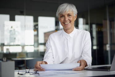 Portrait of content senior businesswoman at desk in her office - RBF07621