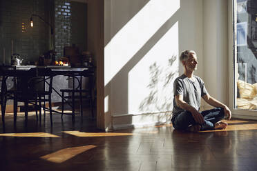 Mature man sitting on the floor at home meditating - MCF00776