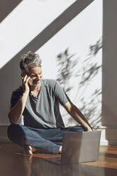 Mature man on the phone sitting on the floor at home with laptop - MCF00779