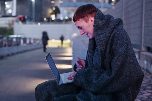 Redheaded young woman using laptop in the city at dusk - MEUF00499
