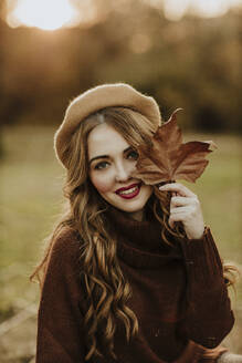 Portrait of fashionable woman with autumn leaf at backlight - GMLF00080