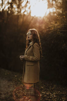 Portrait of fashionable woman in autumn standing at backlight - GMLF00089